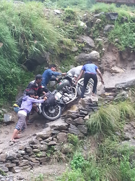 Having to pay locals to carry the bikes up the hillside due to impassable roads