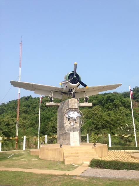 A WWii fighter plain outside a military complex